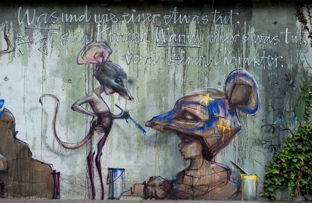 A girl with a rats head and tail carve an image of herself in this street art painting by Herakut