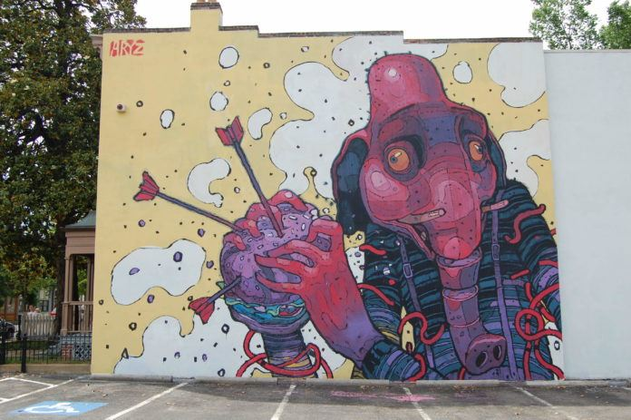 A grahpic style elephant man clutches a hamburger in this street ar mural by graffiti artist Aryz