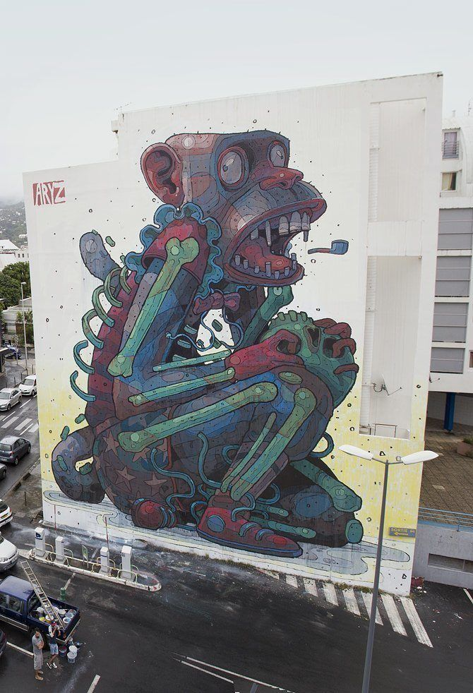 A monkey in shorts and sneakers screeches as he falls apart in this huge street art mural by graffiti artist Aryz