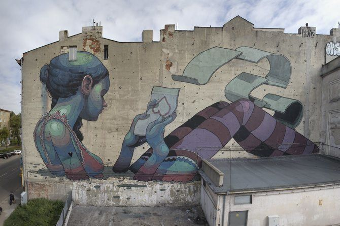 This enormous street art mural by graffiti artist Aryz shows a girl sitting in water reading a love letter