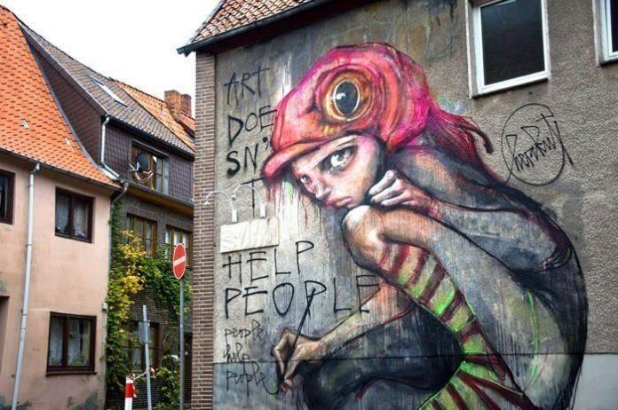This large street art painting by graffiti artists Herakut procalims that art doesn't help people