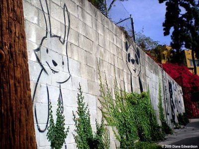 A bunny and a bear peek out from between climbing vines in this friendly street art work by Phil Lumbang