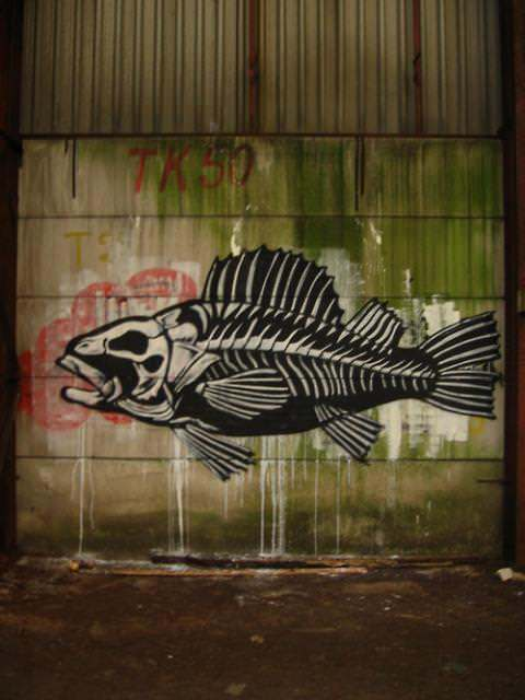 A fish wears its skeleton on the outside in this black and white street art painting by graffiti artist ROA