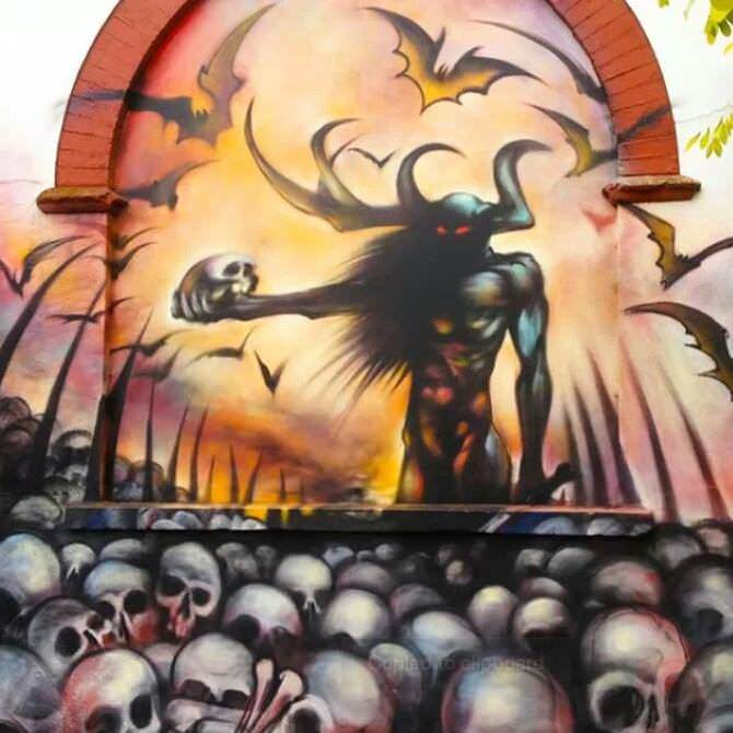 A horned god stands in a hellish graveyard clutching a human skull in this graffiti painting by street artist Jim Vision
