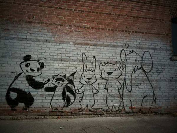 A panda can't paint his own back without a little help from his friends in this street art painting by Phil Lumbang