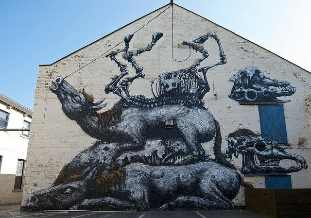 A pile of carcasses and skeletons lie in testament to man's cruelty in this large street art painting by graffiti artist ROA