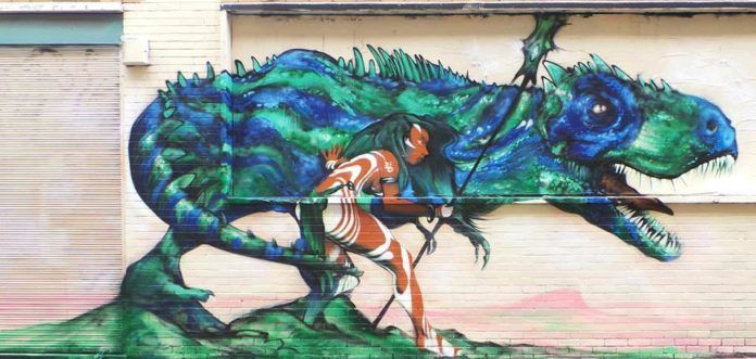 A warrior girl and her companion dinosaur are on high alert in this fantasy graffiti mural by street artist Probs