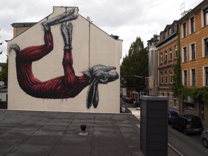 Belgian graffiti artist ROA strings up a skinned rabbit in this enormous anatomical art work