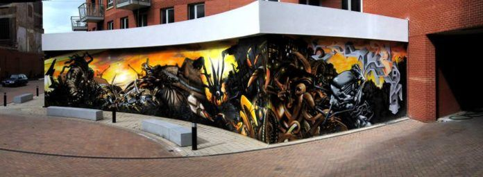 Graffiti artist Jim Vision sprays a street art piece in homage to the famous story War of the Worlds