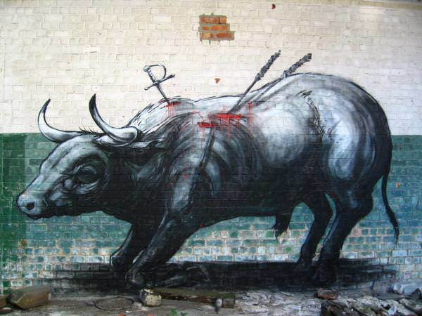 Graffiti artist ROA reminds man of his cruelty toward animals in this street art painting of a toreador bull