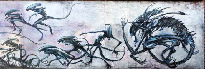 Street artist Jim Vision paints a science fiction graffiti mural depicting the creatures from the famous Alien films charging across the wall