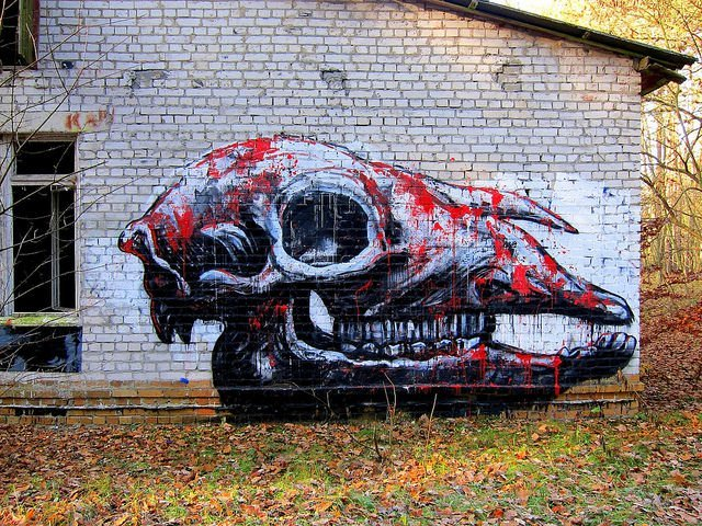 Street artist ROA paints a graffiti art work of a blood spattered animal skull as a reminder of animals that face extinction