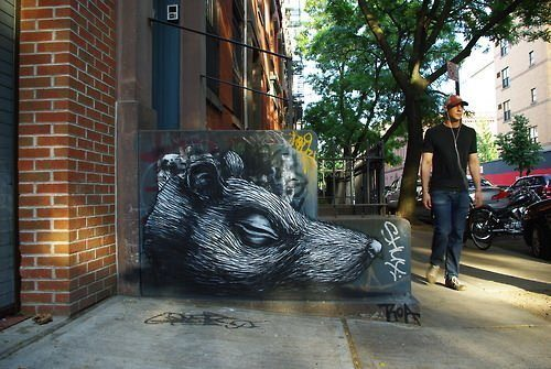This rat's head lies forever silent beside a road in this artist street art painting by graffiti artist ROA