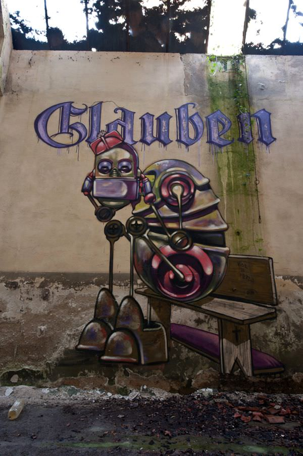 A fed up robot sits beneath the German word for BELIEVE in this street art painting by Pixel Pancho