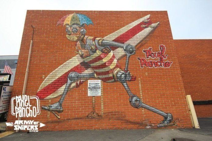A happy robot grabs his surfboard and heads to the beach in this cheerful street art painting by Pixel Pancho
