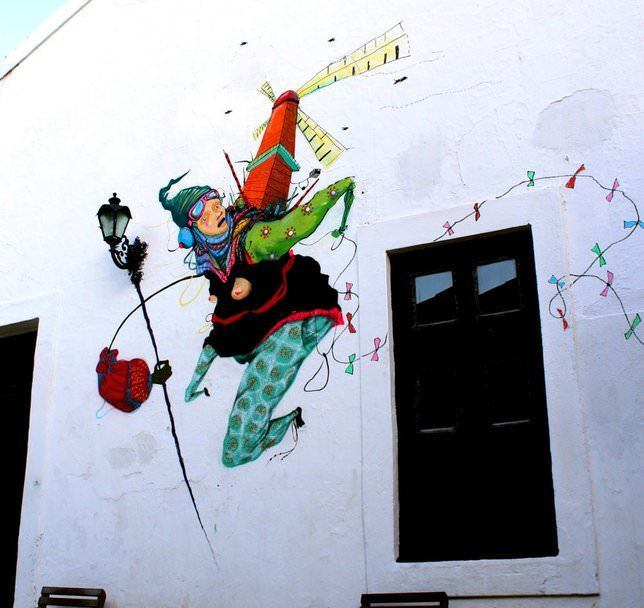 Street artists Grupo Acidum create a graffiti mural that allows this woman to fly with the help of a handy windmill