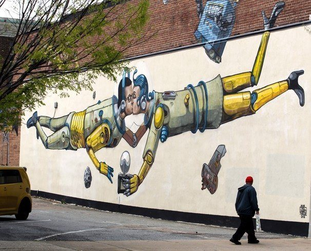 Two robots in love take a selfie of themselves kissing in this social commentary street art work by graffiti artist Pixel Pancho