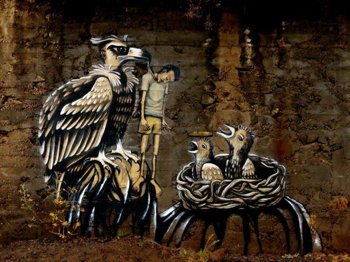 A mother vulture feeds a man to her chicks in this street art mural by Dinho Bento