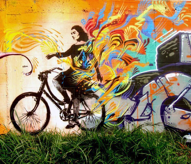 A photograph of a woman riding a bicycle becomes a street art mural by Stinkfish