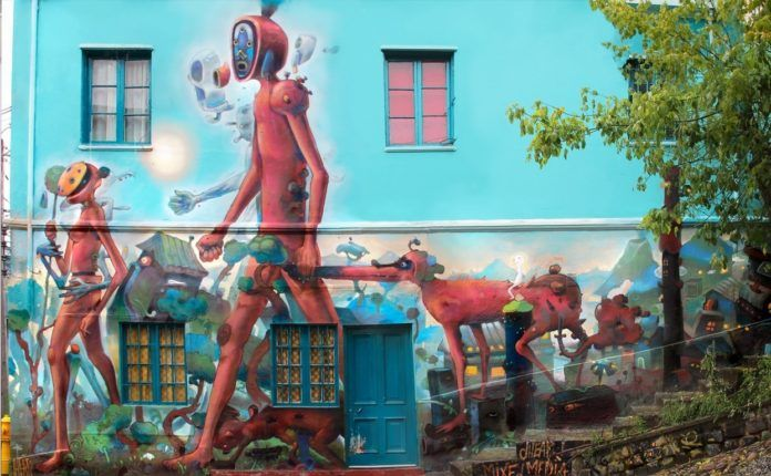 Bizarre humanoid creatures walk through a crazy landscape in this colorful street art mural by Dhear One
