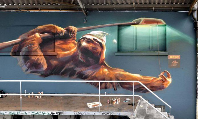 Street artist Wes21 personifies a sloth in this wall mural by giving it a night cap and having it hang from a street light