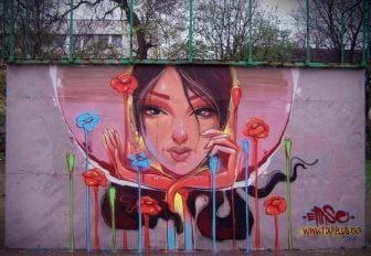 A beautiful girl exists in her own private space bubble in this portrait graffiti piece by Erase