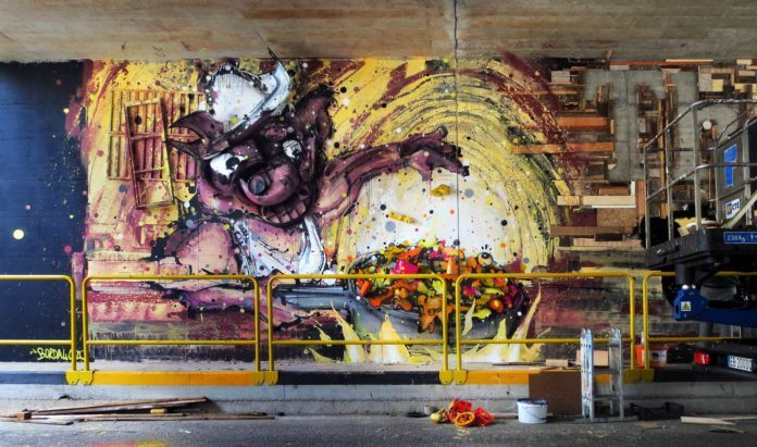 A big pig cooks rats in a frying pan in this sculptural street art mural by Bordalo Segundo
