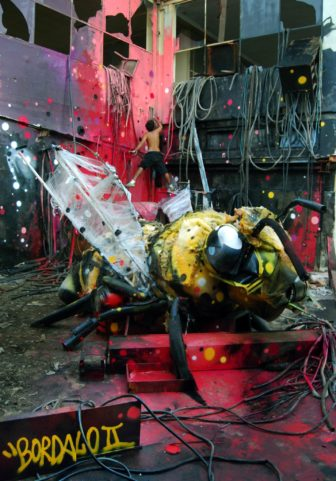 An enormous bee sculpture made out of trash is the central focus of this captivating street art installation by Bordalo