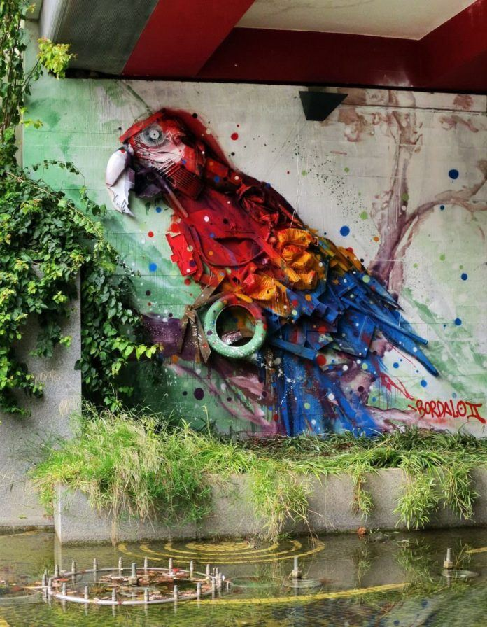 Beneath a bridge a colorful parrot sculpture keeps watch over the water thanks to sculptural graffiti artist Bordalo Segundo