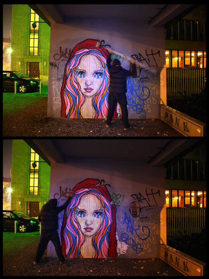 Graffiti Artist El Bocho installs one of his paper and paste street art works under the cover of darkness