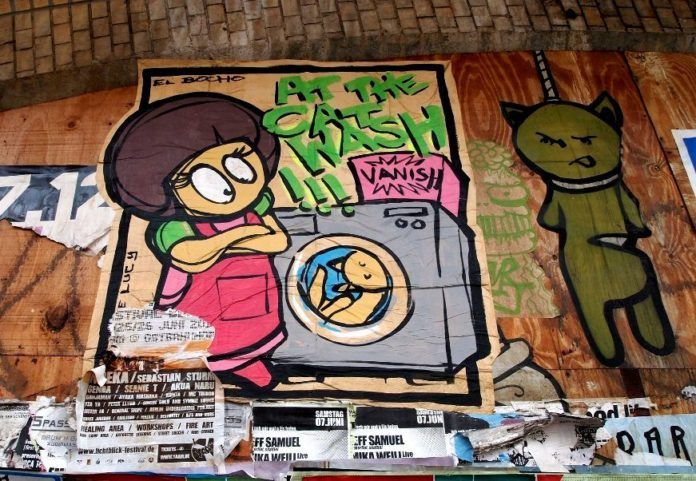 Little Lucy puts her cat in a washing machine in this funny graffiti paste up by El Bocho