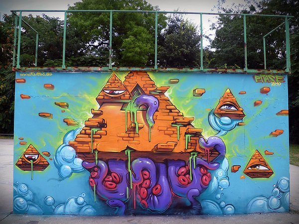 Pyramids and tentacles make up this surreal street art mural in a cartoon style by graffiti artist Erase
