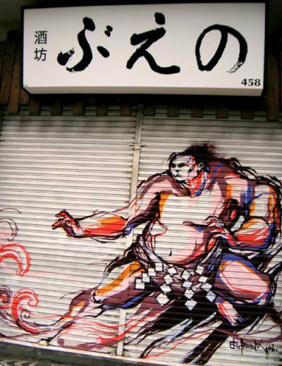 A bulky sumo wrestler wears Titi Freak's street art style in this mural on a garage door
