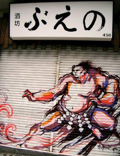 A bulky sumo wrestler wears Titi Freak's street art style in this mural on a garage door