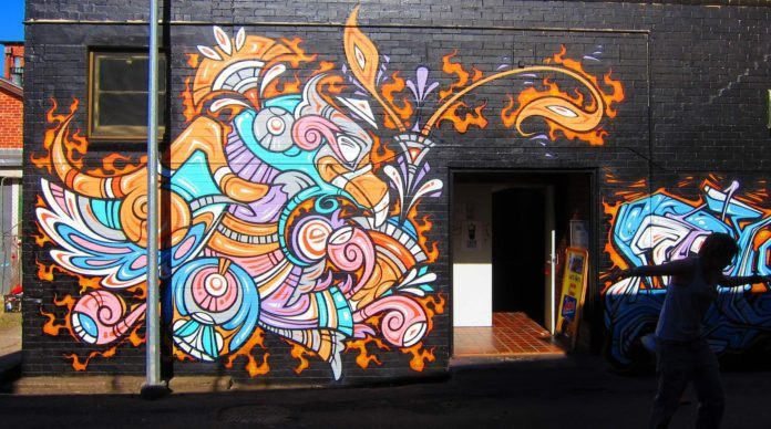 A happy Graffiti phoenix smiles at all who enter in this street art mural by Phibs