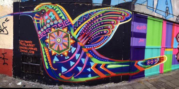 A hummingbird lends its beauty to this wall thanks to the artistic talents of street artist Guache
