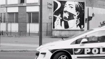 Monsieur Qui completes his poster street art installation moments before the cops arrive
