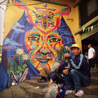 Street artist Guache paints a colorful graffiti mural of a tribal leader with an owl totem