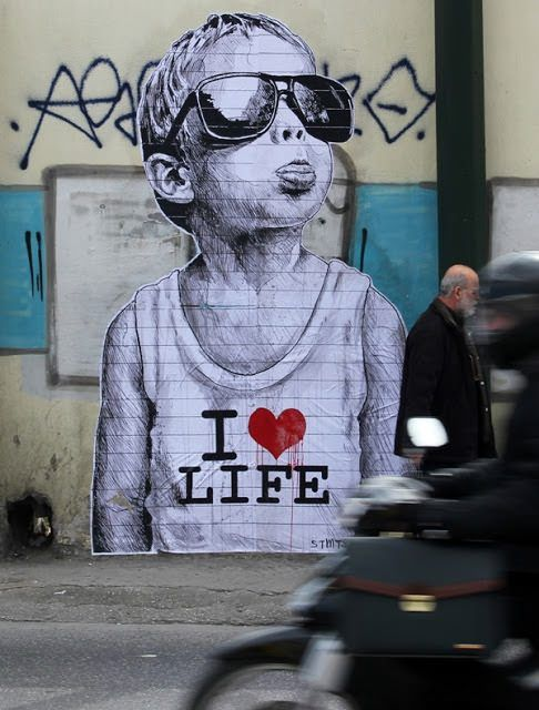 Street artist Stamatis expresses how much he loves life with this powerful poster graffiti art work that features a cheeky little boy