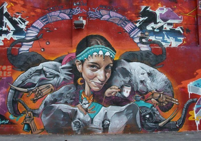 A funny caricature of a young woman looks out in a cheeky way from this fusion graffiti mural by Belin