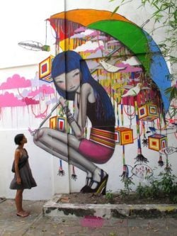 A teenage girl carries an umbrella full of dreams in this colorful street art mural by Seth - in Vietnam