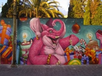 An overexcitable pink elephant celebrates a funny birthday in this colorful street art mural by graffiti artist Duke 103