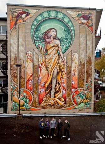 Ashop street artists celebrate the completion of their large scale mural of the Madonna in Montreal