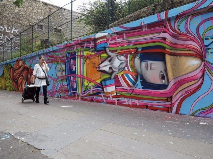 Graffiti artist Seth paints a little French girl in a traditional folk dress in this street art mural in Paris, France