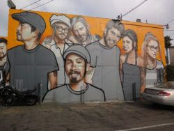 People pose for a party pic in this caricaturized graffiti mural by street artist Belin
