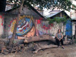 Seth AKA Globepainter creates a graffiti mural of a boy in traditional headdress in Colombia