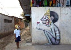 This street art mural in Cambodia is based on the little Cambodian boy who stands beside the mural wearing the same mask as the graffiti character