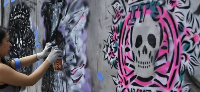 Here is Japanese graffiti muralist Aiko using spray paint and stencils to create her colorful street art
