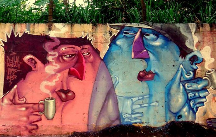 Two graffiti characters enjoy a steaming mug of coffee in this street art mural by Lelin Alves