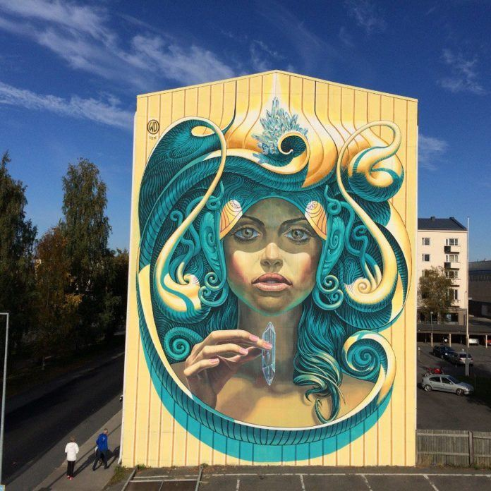 A beautiful woman holds a magic chrystal in this extra large street art mural in Finland by Wild Drawing